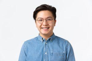 close-up-of-hopeful-cute-asian-guy-with-braces-smi-9EDRS93