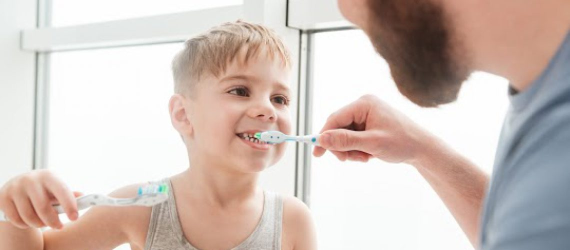 Photo of father and son smiling while brushing teeth in bathroom. Look at each other.