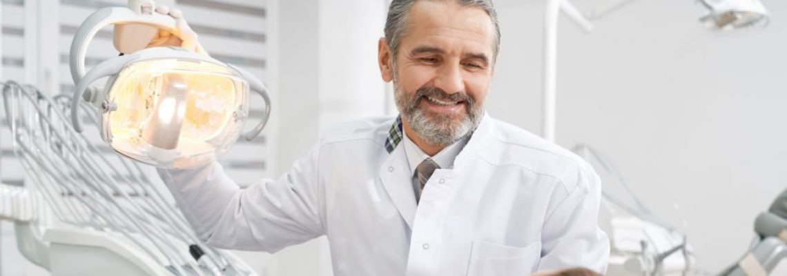 cheerul-dentist-smiling-looking-at-patient-W8ASD5W