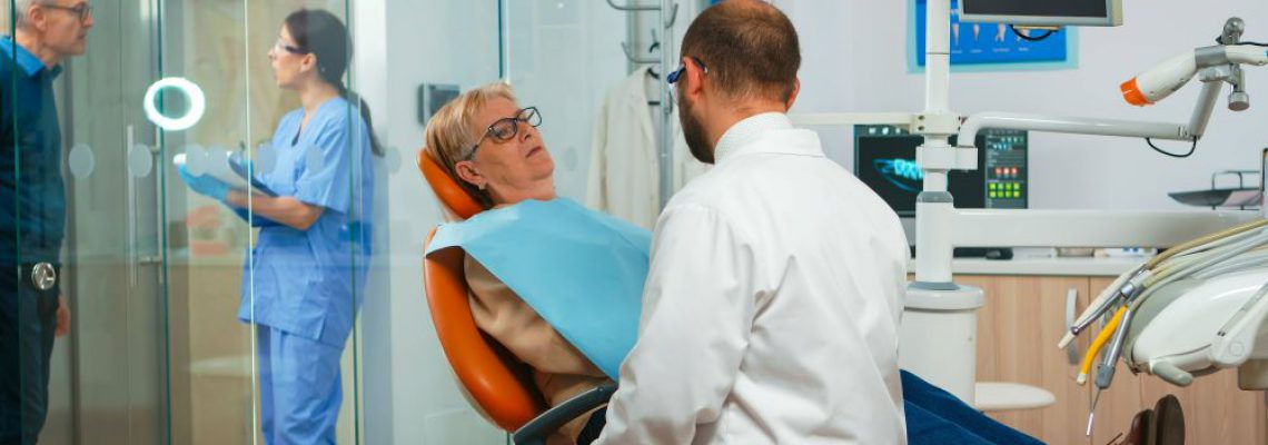 orthodontist-speaking-to-patient-with-toothache-YMBR9L8