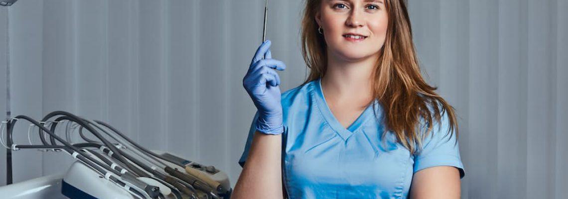 smiling-female-dentist-holding-dental-mirror-while-WHR396Q (1)